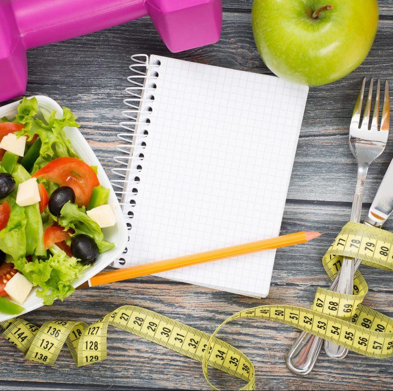 ノート、りんご、サラダ、フォーク、鉛筆、メジャー、ダンベルが置かれている