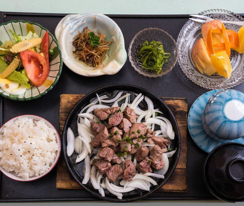 ご飯、サラダ、肉などの定食メニューがテーブルに並ぶ