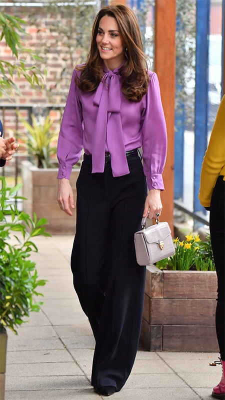 紫のリボンブラウスに黒いワイドパンツ、クリーム色のハンドバックを持ったキャサリン妃