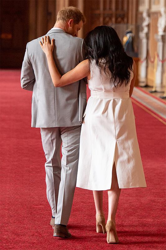 ヘンリー英王子が第一子を抱き、メーガン妃が王子の肩に手を添えて歩いている
