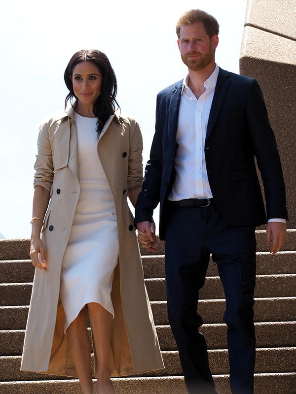 階段を手をつなぎながら降りてくるヘンリー王子とメーガン妃