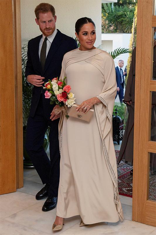 スーツ姿のヘンリー王子と、ベージュのロングドレス姿のメーガン妃