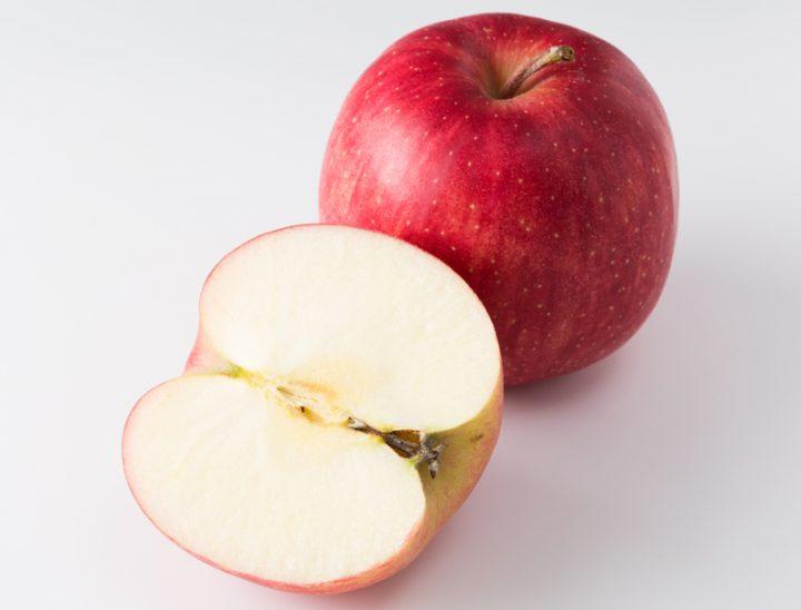 りんごを半分に切ったものと丸ごと1個が置いてある