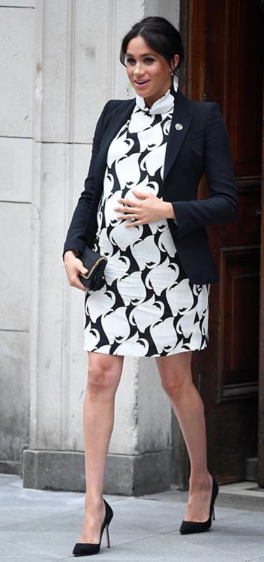 黒地に白い大きな模様が描かれたミニワンピースにジャケットを合わせたメーガン妃が