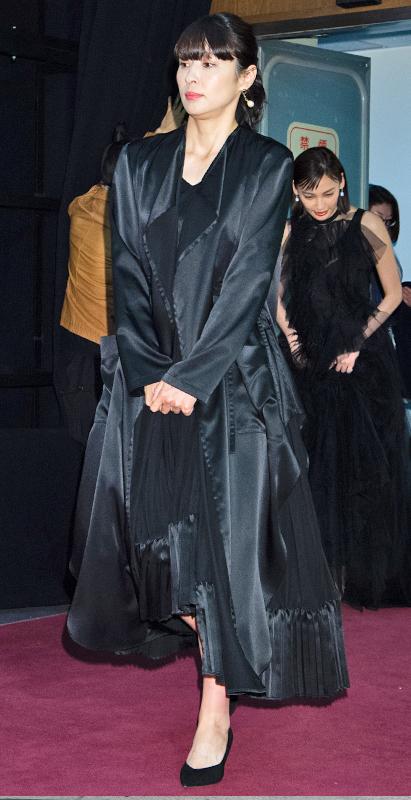 水野美紀が黒のワンピースに黒いジャケットを合わせて着ている