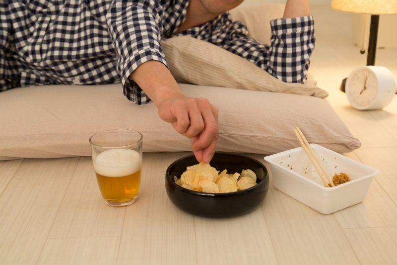 男性が布団に寝ながらビールを飲み、ポテトチップスに手を伸ばし、食べ終わったカップ焼きそばが置いてある