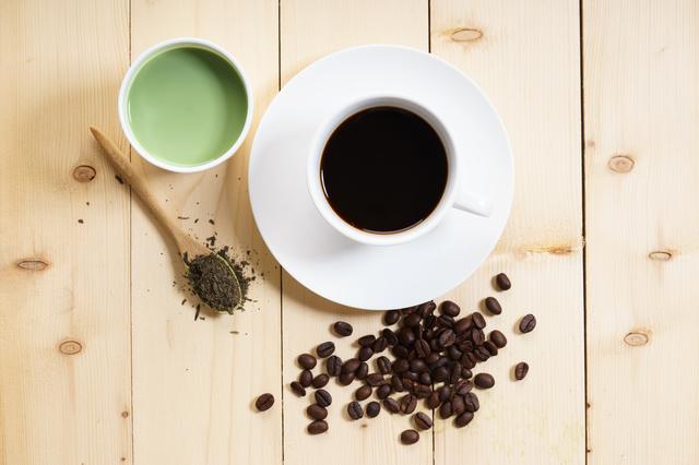 コーヒー豆とホットコーヒー、緑茶とお茶の葉がテーブルにのっている
