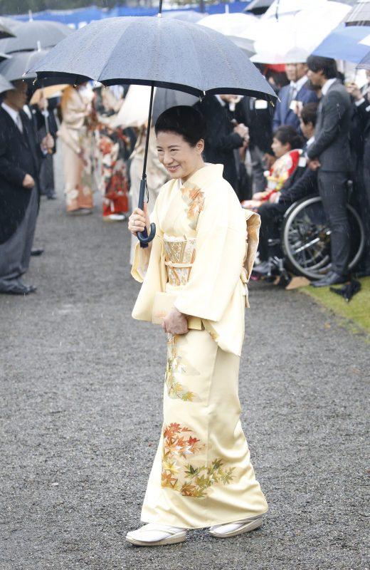 クリーム色の着物姿で傘を差しながら微笑む雅子さま