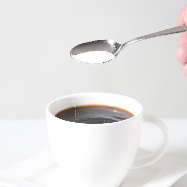 コーヒーにスプーンで砂糖を入れている