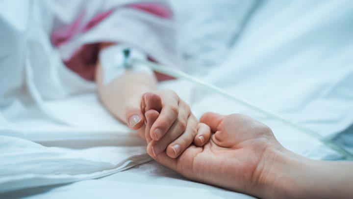 病室のベッドで手を取り合う女性とお見舞いに来た人