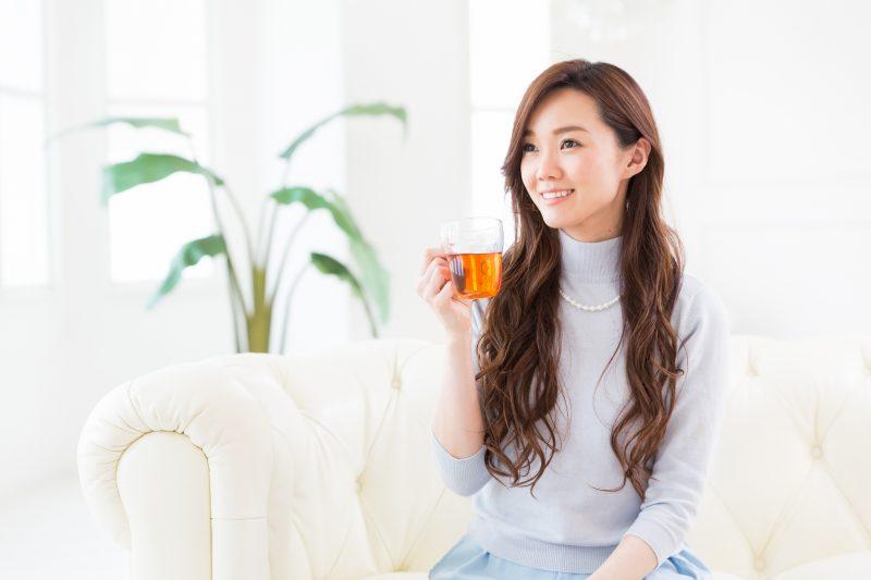 お茶を手に、ソファーでくつろぐ女性