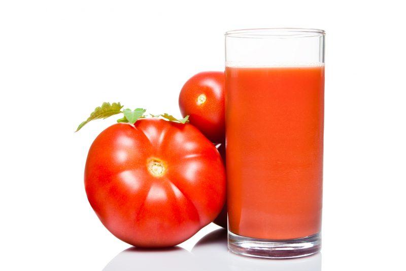 グラスに入ったトマトジュースとトマトの実が並んでいる