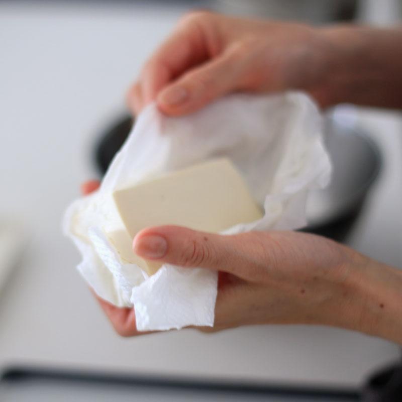 豆腐をキッチンペーパーで水分をとっている