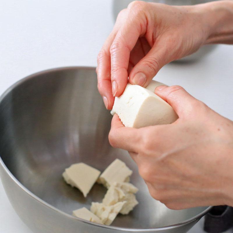 豆腐を手でちいさく切っているところ