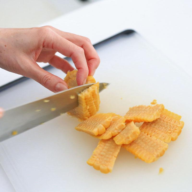 とうもろこしを包丁で切っているところ