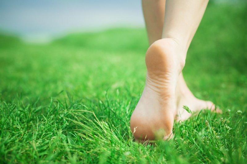 芝生の上に素足で立つ女性