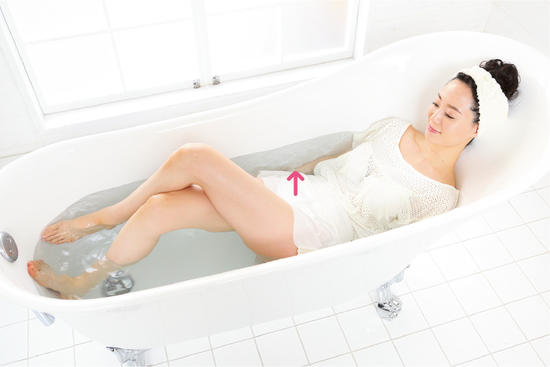 足を湯船に伸ばした状態から、左足を上に組む。お尻を浮かせ、手は体を支える。