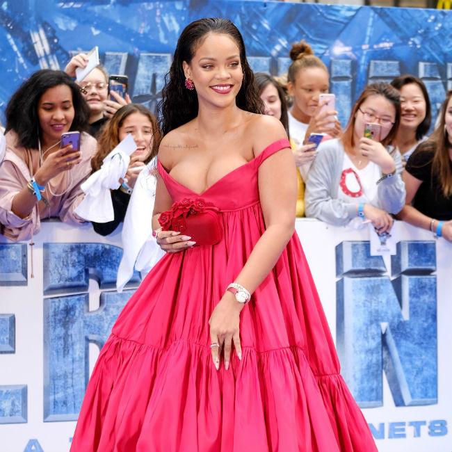 濃いピンクのドレスを着て笑顔のリアーナ