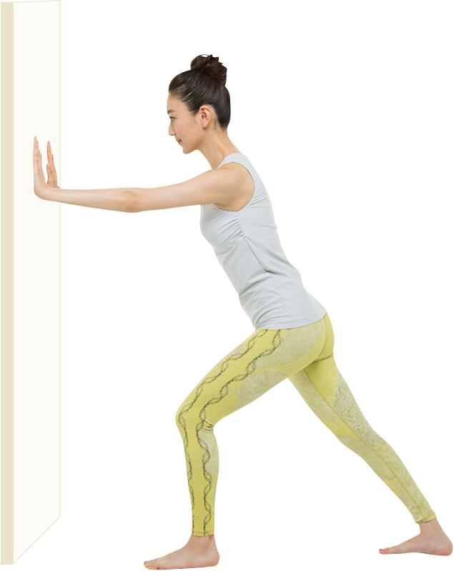 壁を両手で押して、脚を前後に開いて踏ん張っているいる女性