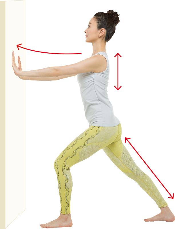 壁を押した状態で姿勢を正してキープしている女性