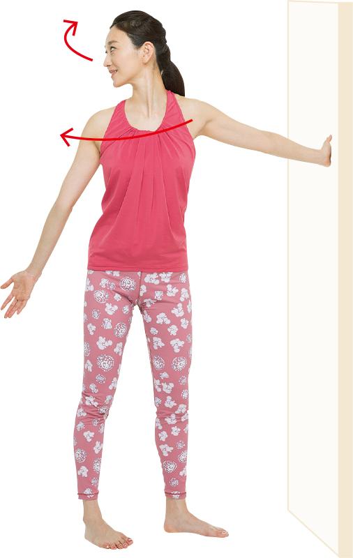 直立して、片手を壁につけて腕を伸ばしている女性