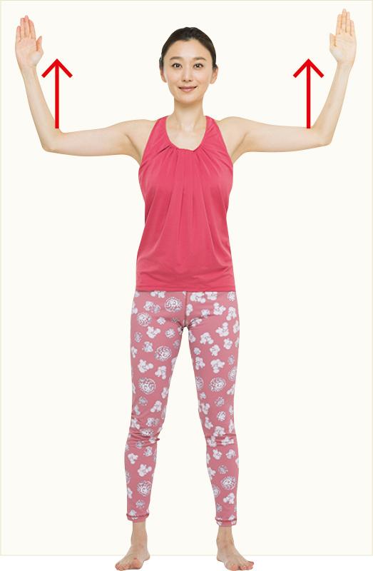 直立して壁に背をつけて、両腕の肘から先上げている女性