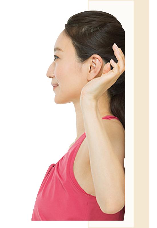 直立して壁に背をつけて、両腕の肘から先を上げている女性だが、手のひらがちゃんと壁についていない