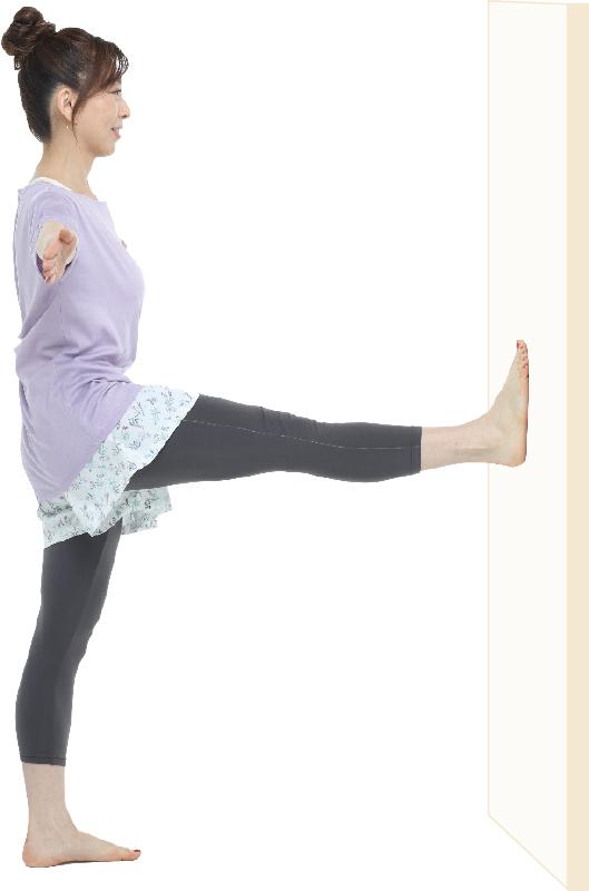 片足で立ち、もう片方の足を正面に上げ、両手を真横に広げている