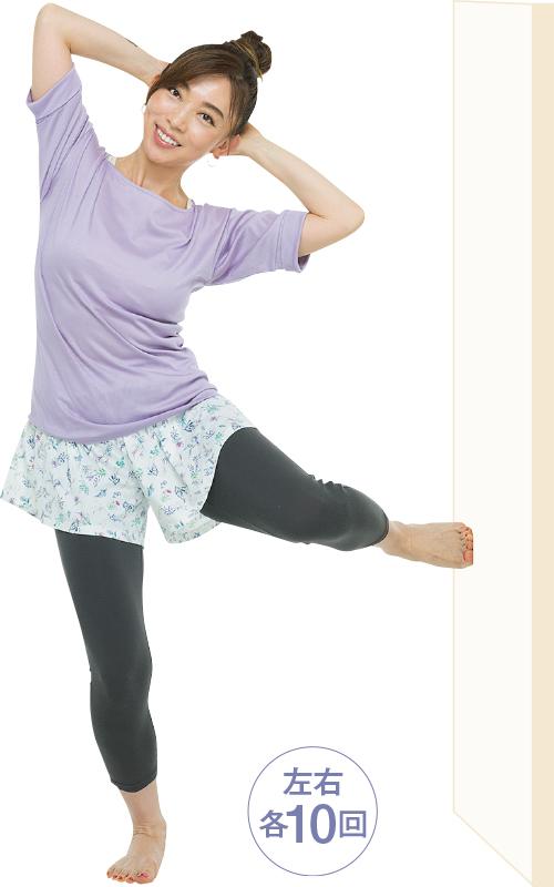 頭の後ろで手を組み、片足で立って、反対の足を壁につけて頭を壁側に倒している女性