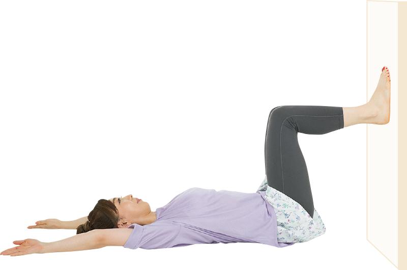 あお向けに寝て足を壁につけ、ひざを曲げている女性