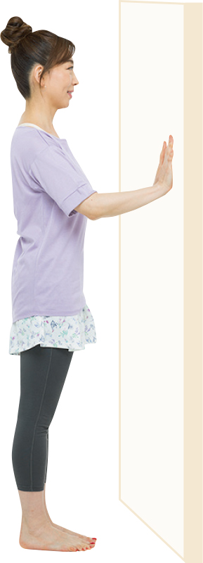 壁に向かって立ち、両手を壁につけている女性