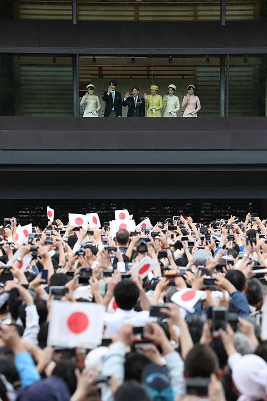 即位後初の一般参賀に臨まれた、天皇陛下、皇后雅子さま、皇嗣さま、紀子さま、眞子さま、佳子さまがそろって笑顔でお手振りをされているのを、日の丸を振っている大勢の人々