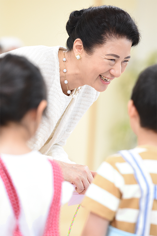 白のジャケットに、チェーンでつないだ大粒の真珠ネックレスを合わせた雅子さま