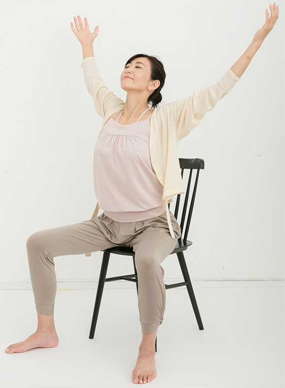いすに座った姿勢で足を開き、両手を斜め上に上げながら、胸を開いて息を吸う
