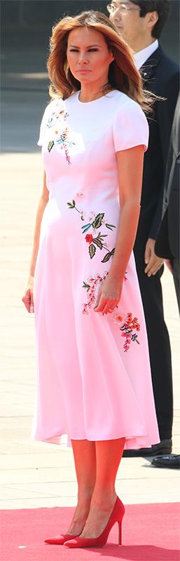 白地に様々な花が刺繍されたワンピースを着たメラニア夫人がレッドカーペットに立っている