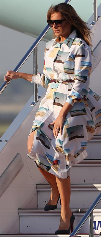 白地に様々な風景の写真がプリントされたシャツワンピースでタラップからおりてくるメラニア夫人