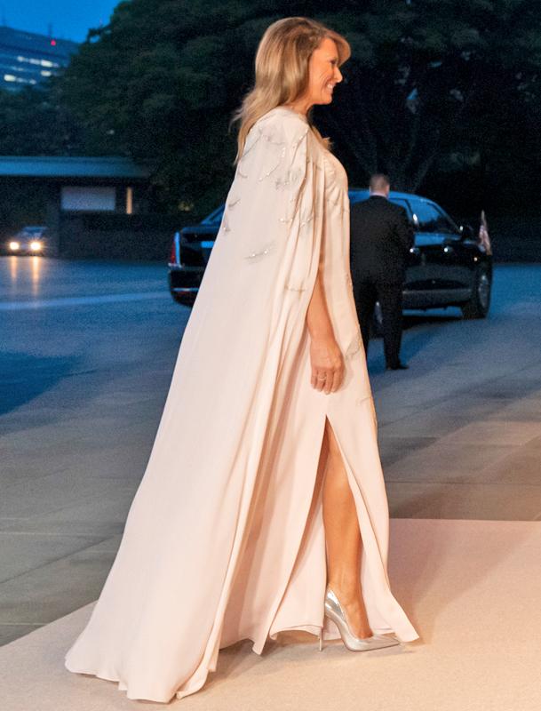 薄いピンクベージュの長いガウンのついたロングドレスを着たメラニア夫人
