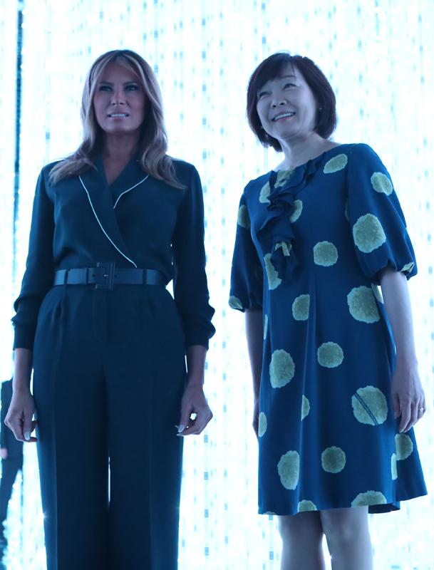 紺色のジャンプスーツを着たメラニア夫人と、黒地に大きな水玉模様のワンピースを着た安倍昭恵夫人