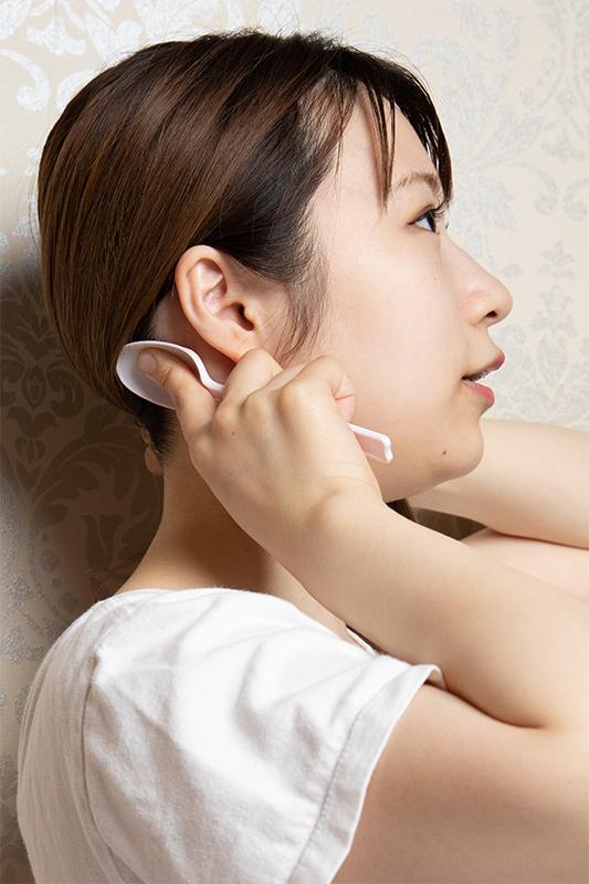 耳の後ろの生え際にスプーンを当てた女性