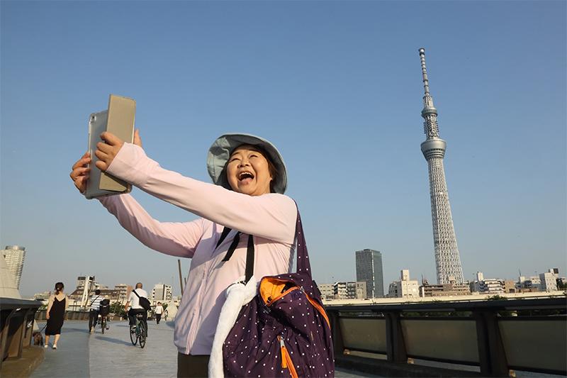 スカイツリーをバッグに自撮りするオバ記者