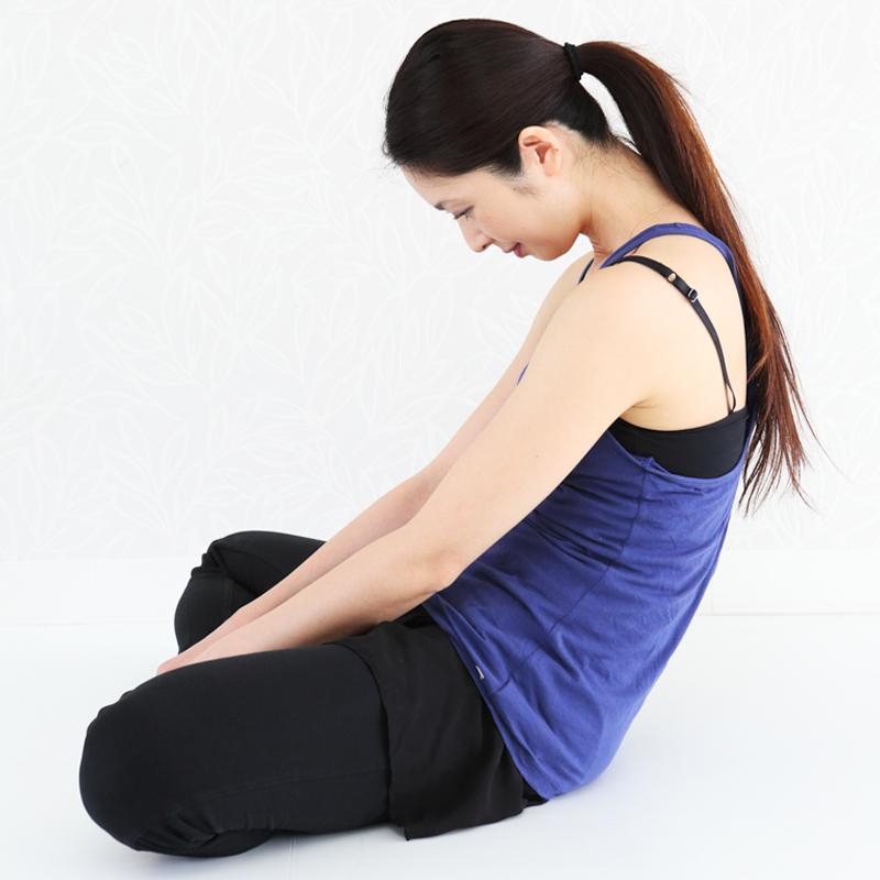 胡坐をかいて足首を持って骨盤を倒すように後ろへ重心をかける女性
