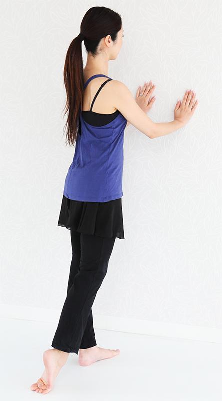 壁にまっすぐ向かって立ち、両手を壁について、片足の甲を地面につけて伸ばしている女性