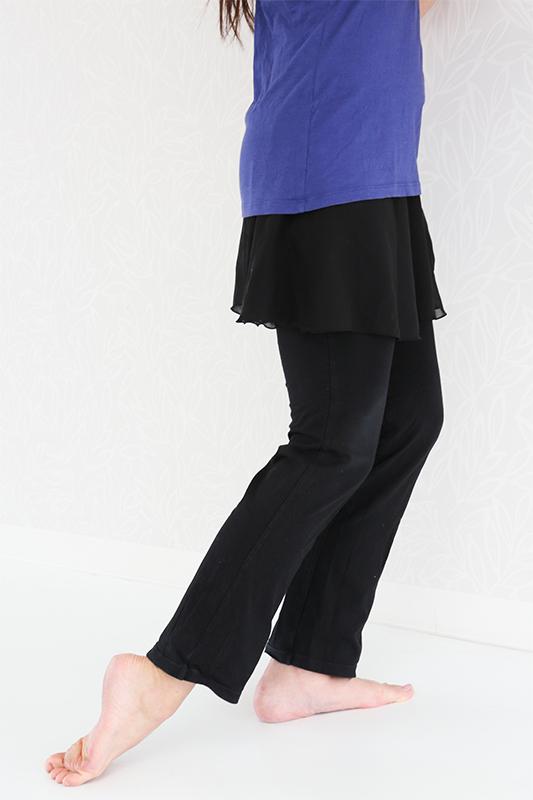 基本の立ち方から軸足になったほうのひざを少し曲げ、足の甲を地面について足首を伸ばしている女性