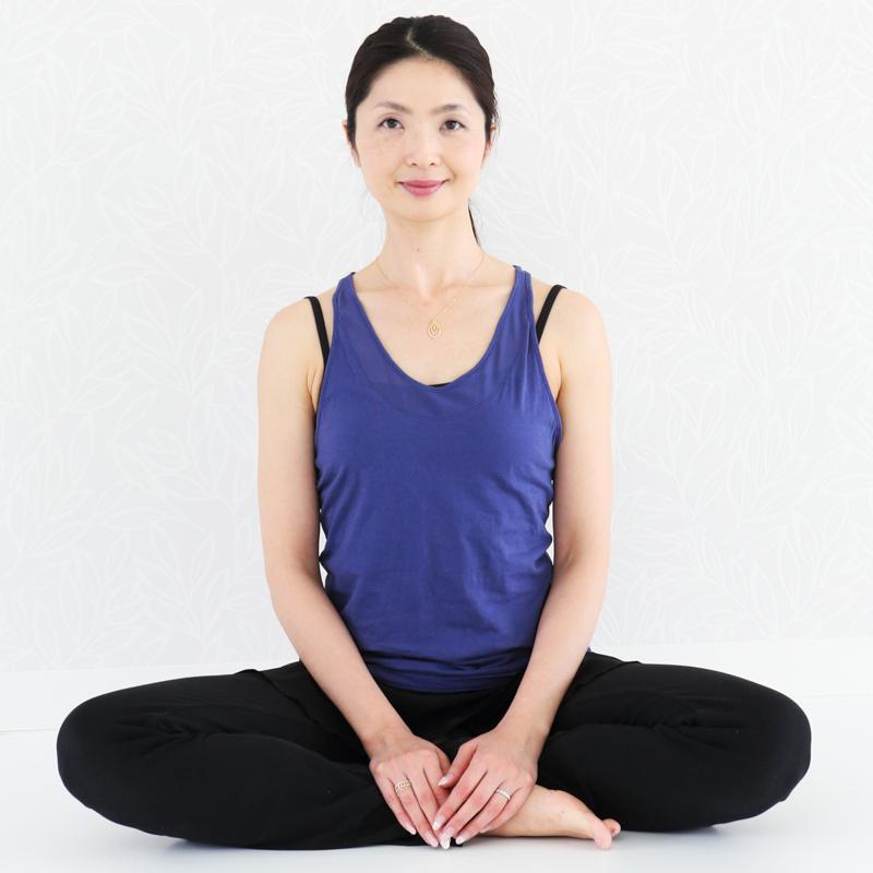 胡坐をかいてピンと背筋を伸ばして座る女性