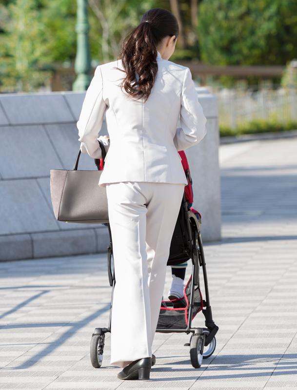 パンツスーツでベビーカーを押しながら通勤している女性の後ろ姿