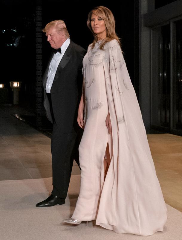 タキシードのトランプ大統領と一緒に歩く、薄いピンクベージュの長いガウンのついたロングドレスを着たメラニア夫人。