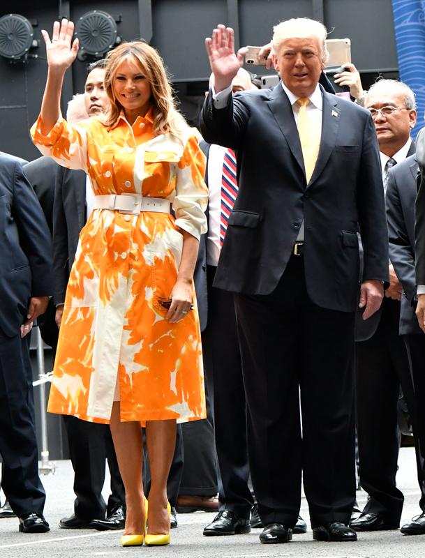 スーツ姿のトランプ大統領と白地にオレンジ色の大きな花が描かれたコートを着たメラニア夫人が手を振っている