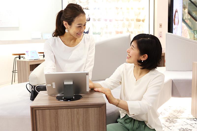 iPadを見ながら笑顔で説明する女性と、笑顔で話を聞く女性