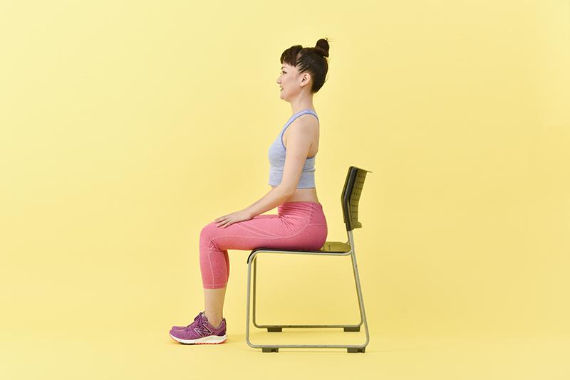 椅子に浅めに腰掛け背筋をまっすぐにする女性