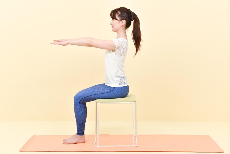 椅子に座り両手をまっすぐ前に出す女性